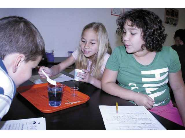 Faith Vizza, center, adds salt to colored water while James Spencer, left, and Genesis Velez watch to see if it dissolves during a science experiment at Mint Canyon Elementary School in Canyon Country. The experiment was part of the Quest for Science program.