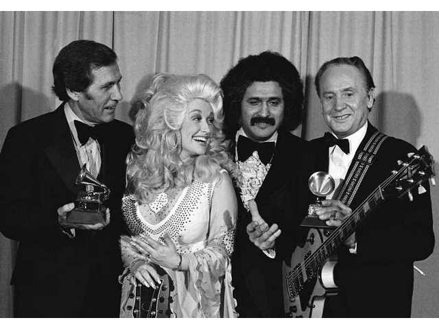 In this Feb. 19, 1977 file photo, Les Paul, right, and Chet Atkins, left, are presented Grammys by Dolly Parton and Freddie Fender, second from right, at 19th annual Grammy Awards in Los Angeles. Paul, 94, the guitarist and inventor who changed the course of music with the electric guitar and multitrack recording and had a string of hits, died Thursday, Aug. 13, 2009 in White Plains, N.Y.