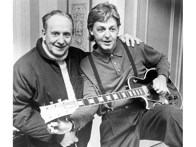 "In this May 3, 1988 file photo, Paul McCartney, right, tries out a custom-made left-handed ""Les Paul Lite"" guitar presented to him by designer, Les Paul, left, in New York. Paul, 94, the guitarist and inventor who changed the course of music with the electric guitar and multitrack recording and had a string of hits, died, Thursday, Aug. 13, 2009 in White Plains, N.Y."