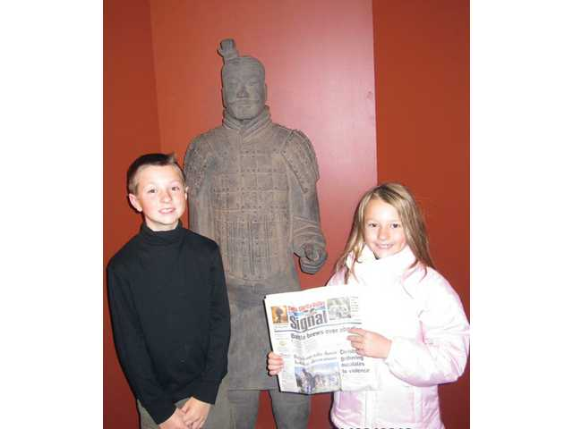 Fourth-grader Jon Matkin and his second-grade sister Laine Matkin, stand in front of a terra cotta warrior inside the National Geographic Museum in Washington, D.C., on Jan. 6.