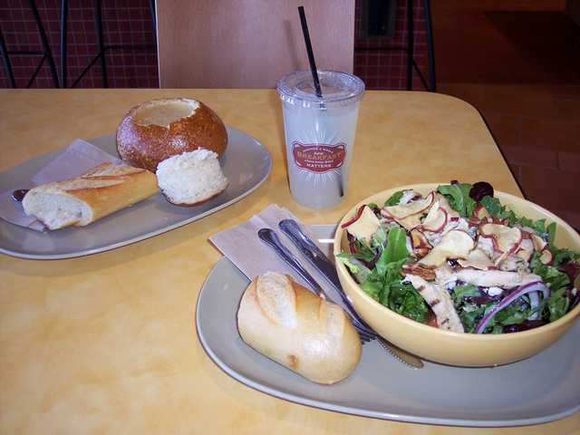 "Broccoli chedder soup in a bread bowl ($5.49) is served with a baguette and the Fuji apple chicken ""signature"" salad ($7.99)."