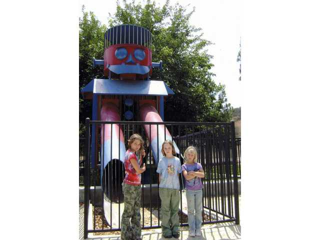 Hannah Bayer, left, Bailey Volk, center, and Sarah Bayer stand in front of the Robot Slide at Seco Park. The slide is fenced off to prevent children from playing on it since it was deemed unsafe.