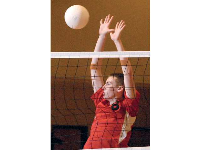 Santa Clarita Christian volleyball player Owen Jessup jumps at the net for a block against Cate on March 5.
