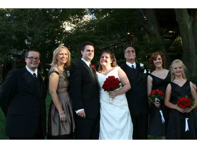 The newlyweds (center) pose with the bride's immediate family (from left): Robbie and Karla Posner; David, Samantha and Kimberlee Posner.