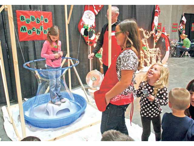 Grace Prabhu, 6, of Stevenson Ranch, left, tries the Bubble Machine in the children's craft area at the Festival of Trees event on Friday.