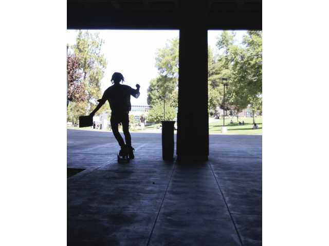 A skateboarder rushes to class on his first day of school at College of the Canyons on Monday.