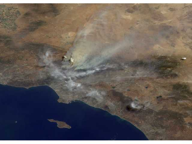 This image of the Station Fire was acquired mid-morning Aug. 30 by NASA's Terra satellite. The approximate perspective view is at an angle of 46 degrees off of vertical. The area covered is 152 miles wide. Several pyrocumulus clouds, created by the fire, are visible above the smoke plumes rising from the San Gabriel Mountains north of Los Angeles in the left-center of the image. Smoke covers the interior valleys along the south side of the San Gabriels, along with parts of the city of Los Angeles and Orange County, and drifts for hundreds of miles to the east over the Mojave Desert.