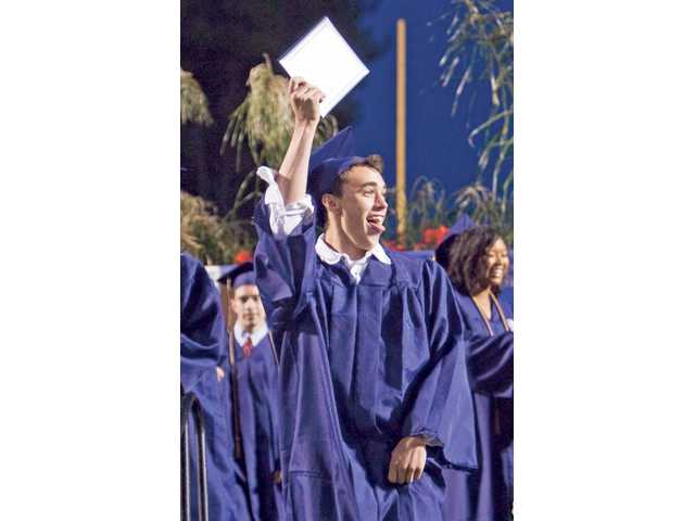 Jeff Slocum waves to his friends and family after receiving his diploma at the West Ranch High School graduation ceremony.