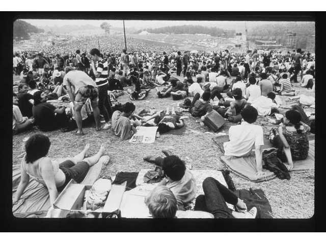 """The stage was a distant spec from the edges of the audience at the Woodstock Music& Art Fair Aug. 15, 16 and 17, 1969, in White Lake, N.Y. as seen in a photo from """"The Woodstock Experience""""; by Michael Lang and Henry Diltz, released by Genesis Publications in June 2009 to mark Woodstock's 40th anniversary."""