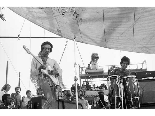 """Jimi Hendrix plays at dawn on Sunday, Aug. 17, 1969, the third and final day of the Woodstock Music & Art Fair in White Lake, N.Y., as seen in a photo from """"The Woodstock Experience"""" by Michael Lang and Henry Diltz, released by Genesis Publications in June 2009 to mark Woodstock's 40th anniversary."""