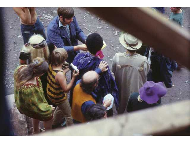 """Jimi Hendrix is surrounded by fans under the stage after his performance on Sunday, Aug. 17, 1969, the third and final day of the Woodstock Music & Art Fair in White Lake, N.Y., as seen in a photo from """"The Woodstock Experience"""" by Michael Lang and Henry Diltz, released by Genesis Publications in June 2009 to mark Woodstock's 40th anniversary."""