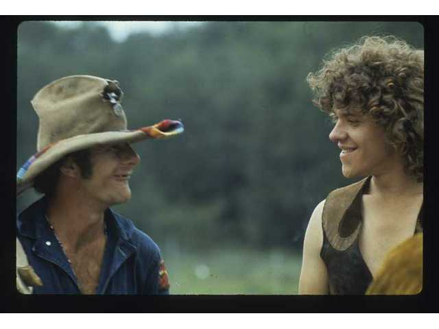 """The Hog Farm's Wavy Gravy and festival producer Michael Lang cross paths during the Woodstock Music & Art Fair in White Lake, N.Y., Aug. 15, 16 and 17, as seen in a photo from """"The Woodstock Experience"""" by Michael Lang and Henry Diltz, released by Genesis Publication sin June 2009 to mark Woodstock's 40th anniversary."""