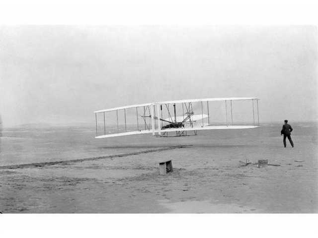 The Wright biplane, piloted by Orville Wright, has just taken off from a monorail launching strip on a field at Kitty Hawk, N.C. on Dec. 17, 1903. Wilbur Wright, running along the right side of the aircraft, held onto the wing to balance the machine until it left the monorail.