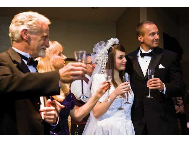 "The ""wedding party"" lifts their glasses as a toast is given for the new couple during a dress rehearsal Monday night for the play ""When It's Gone,"" being put on by New Life Assembly of God."