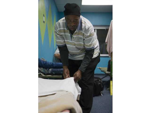 Fred Turner, of Kern County, gets his bed ready at the Santa Clarita Homeless Shelter.