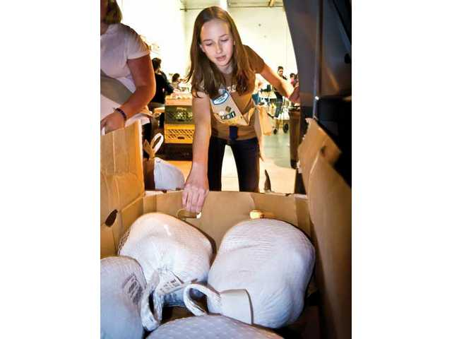 Shelby Goodfellow a 13 year old from Valencia and member of troop 291 helps to give out turkeys at the Hunger Defense Funds donation and pick up center in Canyon Country.