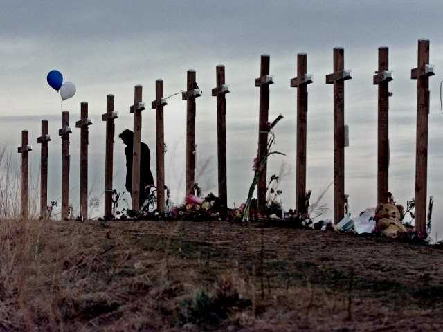 <p>In this April 28, 1999, file photo, a woman stands among crosses posted on a hill above Columbine High School in Littleton, Colo., in remembrance of the 15 people who died during a school shooting on April 20, 1999. Associated Press photo</p>