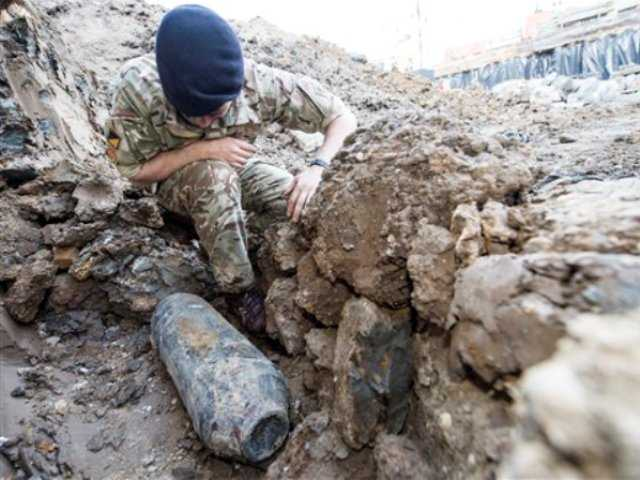 <p>An army bomb disposal expert inspects an unexploded World War II bomb found in Wembley, north London, Thursday May 21, 2015. The 50-kilogram (110-pound) bomb was discovered by workers at a construction site near Wembley stadium.</p>
