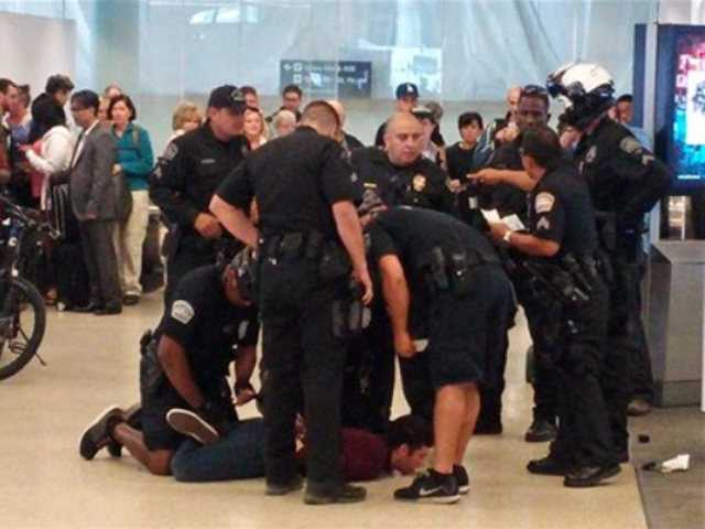 <p>Police officers restrain a man they used a stun gun on at Los Angeles International Airport, Wednesday. Airport police Sgt. Belinda Joseph said the man who was stunned had refused to cooperate with Transportation Security Administration officers at Terminal 6.</p>