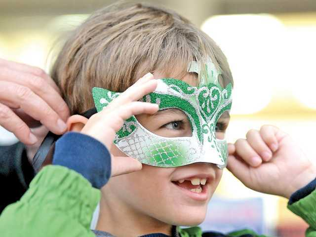 <p><span>Jadon Savell, 7, smiles as he dons a masquerade mask, provided by the city of Santa Clarita, at the Masquerade-themed Senses event in downtown Newhall on Thursday. </span><em>Signal photo by Katharine Lotze</em></p>