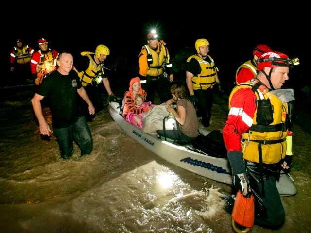 <p>From left, Mark Norris, Retha Norris, Ally Smith, 4, and Christina Norris, are rescued by firefighters after they clung in a tree at their home on South Old Stagecoach Drive in Kyle, Texas during a flood on Sunday.</p>