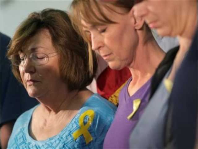 <p>Marry Ann Charba, left, and Kim Charba, right, join other in prayer during a news conference for families of the victims of recent severe weather, Thursday, in Wimberley, Texas. At least eight people are missing in Hays County.</p>