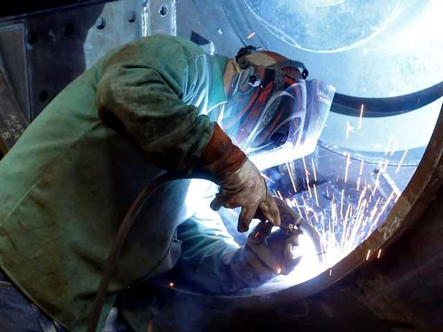 <p>A man welds parts in fans for industrial ventilation systems at the Robinson Fans Inc. plant in Harmony, Pa. <span>The U.S. economy shrank at a 0.7 percent annual rate in the first three months of the year, depressed by a severe winter and a widening trade deficit.</span></p>
