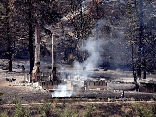 <p>The foundation and chimneys from a destroyed home continue to smolder following a wildfire in Wenatchee, Wash.</p>