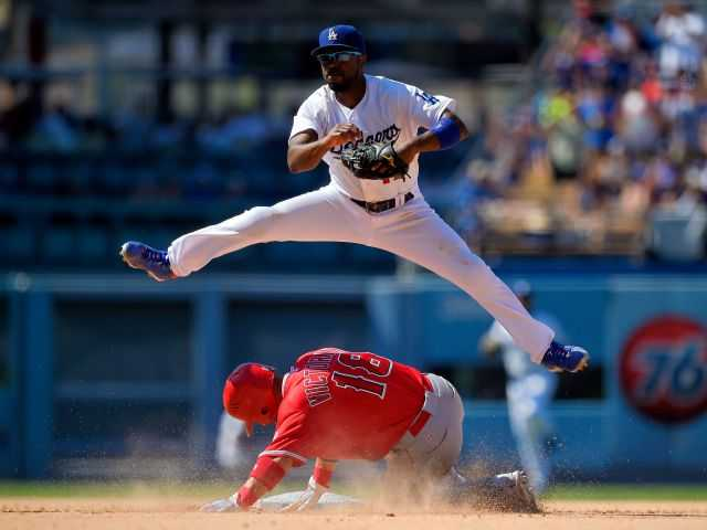 <p>Los Angeles Angels Shane Victorino, below, is forced out at second as Los Angeles Dodgers shortstop Jimmy Rollins attempts to throw out Erick Aybar at first during the ninth inning of a baseball game, Sunday,  in Los Angeles. Aybar was safe at first on the play. </p>