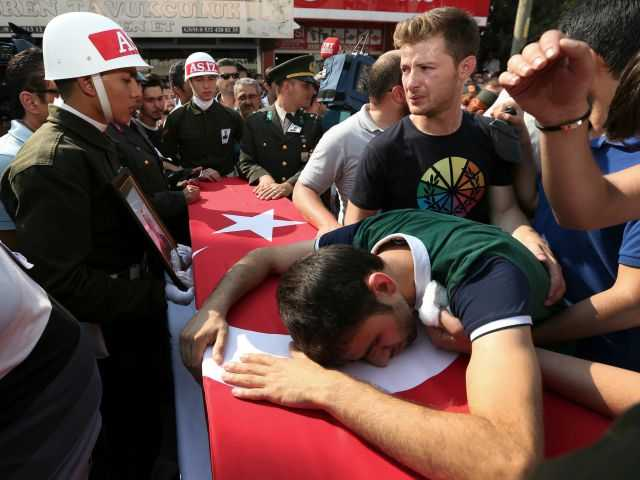 <p>A relative cries over the Turkish flag-draped coffin of Turkish soldier Kagan Kandemir, during his funeral in the town of Civril, Turkey, Friday, July 31, 2015. </p>
