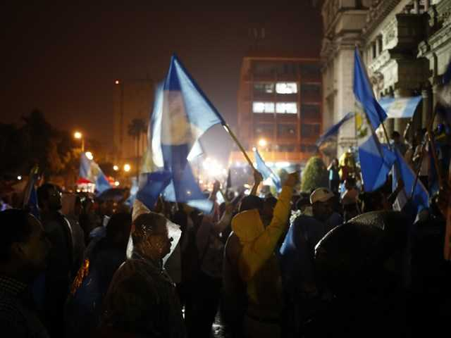 <p>Demonstrators wave Guatemalan flags in Guatemala City on Tuesday as they celebrate that Congress voted to withdraw President Otto Perez Molina's immunity from prosecution.</p>