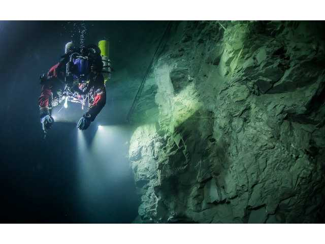 <p>In this underwater photo taken Aug. 21, 2015, in the flooded Hranicka Abyss, Czech Republic, Polish explorer Krzysztof Starnawski is seen examining the limestone crevasse and preparing for a 2016 expedition to measure it depths. </p>