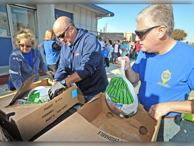 "<p>Volunteers in the Santa Clarita Valley took the ""giving"" part of Thanksgiving to heart Tuesday as they handed out hundreds of turkeys to needy local families ahead of the holiday.</p>"