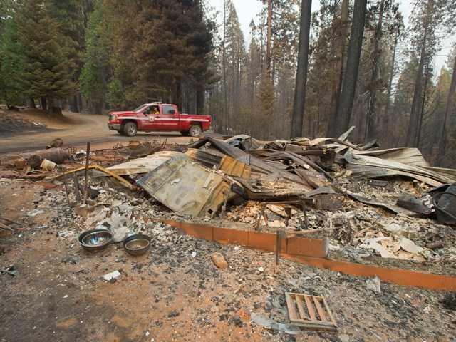Teams assess damage as California wildfire burns