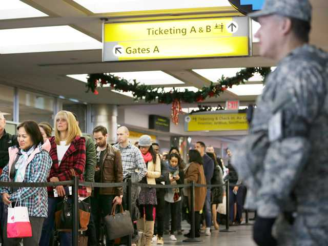 <p>Security personnel watch as passengers wait to pass through airline security at LaGuardia Airport in New York. (AP Images)</p>