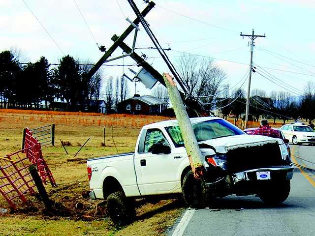 Rhodes injured when pickup strikes pole