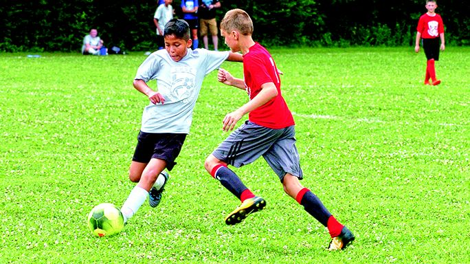 Storm Trooper Eric Hernandez fends off an attack by Red Dragon Aiden Malone in the semi-finals of the Center Hill Youth Soccer League this past Saturday.