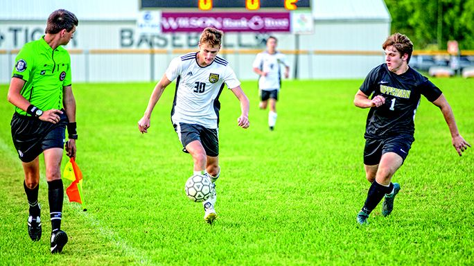 Luke Bryant is pursued by an Upperman player as he attacks on offense under the watchful eye of the line judge during the finals of the district tournament.