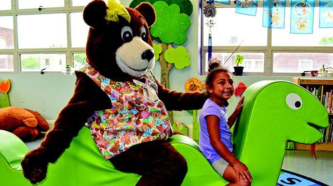 Bonnie Bear couldn't resist joining 5-year-old Khloe Howell on the bookwork in the children's library.