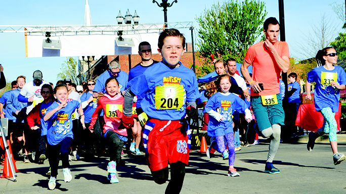 Corbin Felton takes off to lead the pack of nearly 500 participants Saturday morning at the start of the Queens for a Cause Autism 5K in downtown McMinnville.