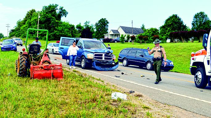 The Highway Patrol investigates the crash scene Wednesday morning on Highway 56 where a Dodge Durango rammed the back of a John Deere tractor driven by Garry Wayne Grissom.