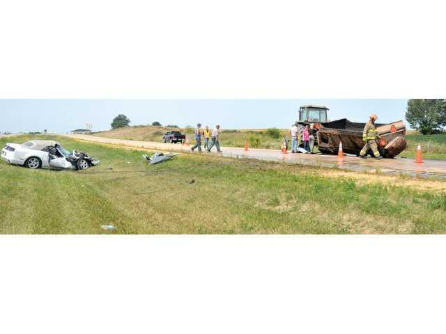 Car hits manure spreader