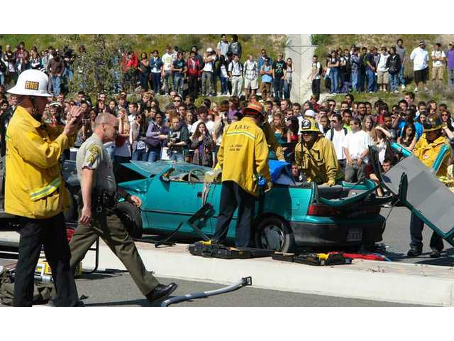 "Fire department personnel work to disassemble one of the vehicles involved in the simulated crash. The ""Every 15 Minutes"" program is a two-day event designed to make the consequences of drunk driving clear to high school students."